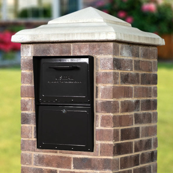 Black locking mailbox installed in brick